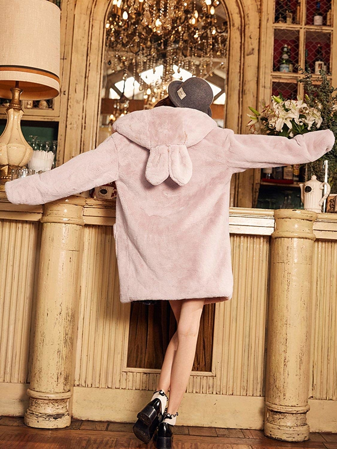 A model showing the back of the pink hooded coat with bunny ears