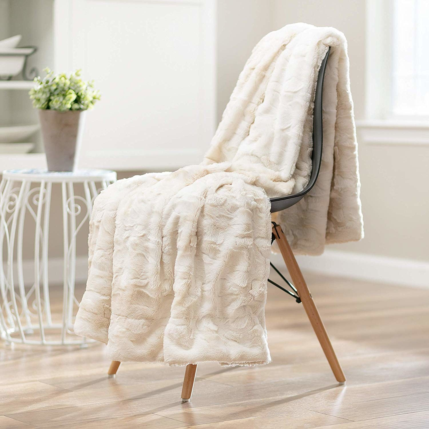 The throw blanket laid on a chair.