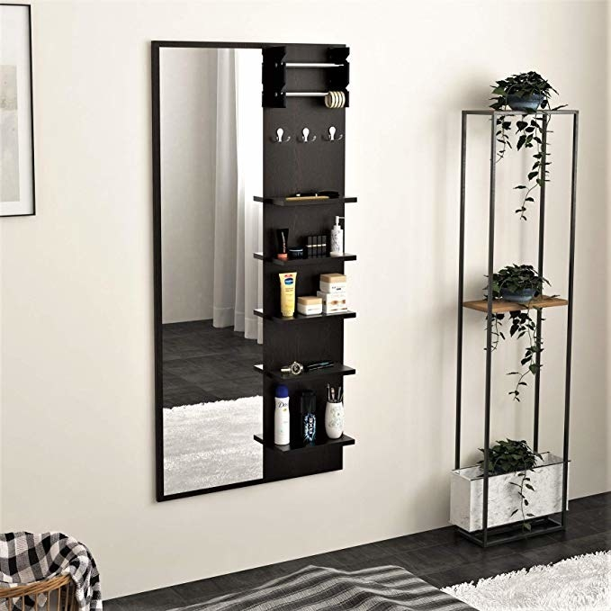 A tall mirror with shelves on it sides, holding cosmetics and toiletries