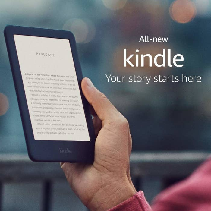 A hand holding the black Kindle
