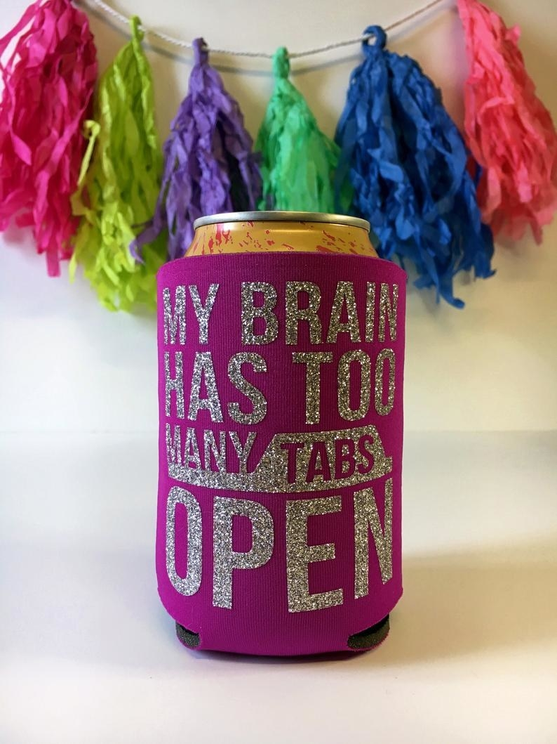 """pink coozie with silver glitter on it that says """"my brain has too many tabs open"""""""