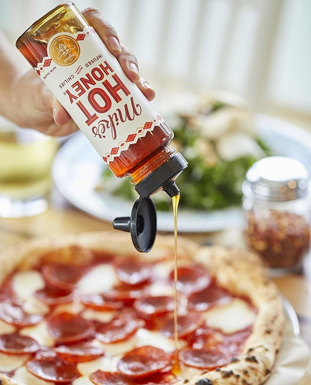 hand sqeezing a bottle of the hot honey on a pizza