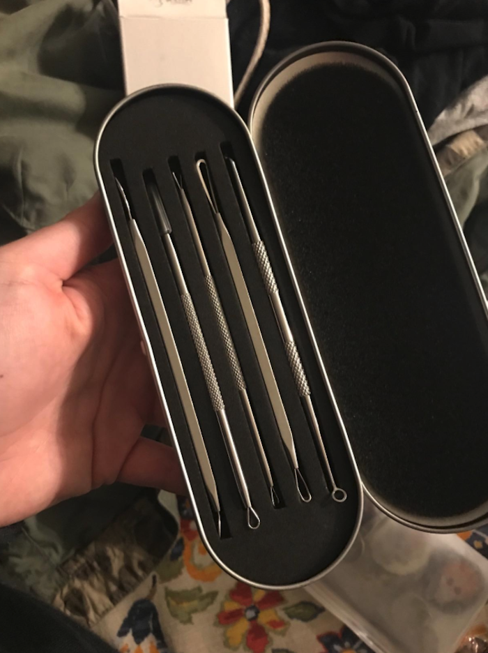 a hand holding the case that's shaped like an eyeglass case. It has slots that hold each tool.