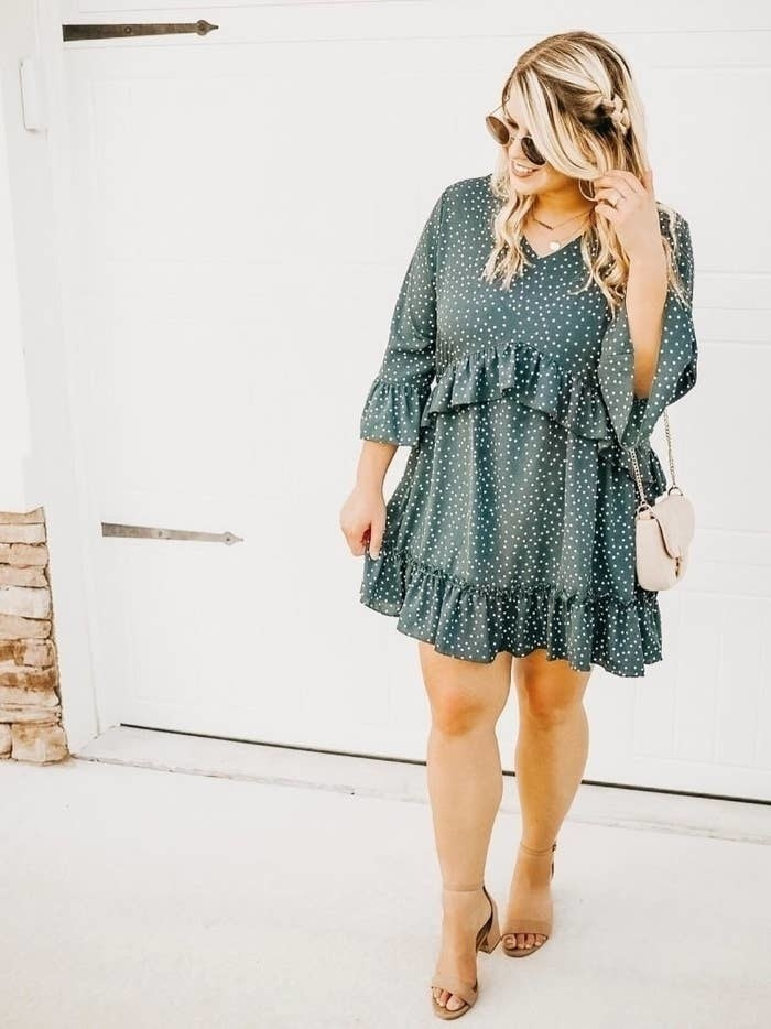 Reviewer wearing the v-neck dress with ruffles under the bust and around the hem in green with small white dots