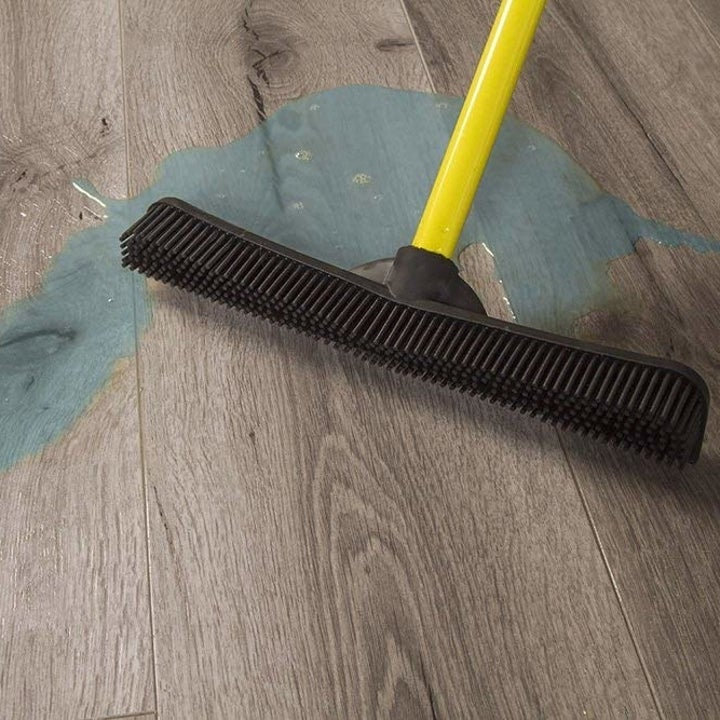 the broom sweeping up coffee grounds from a hardwood floor