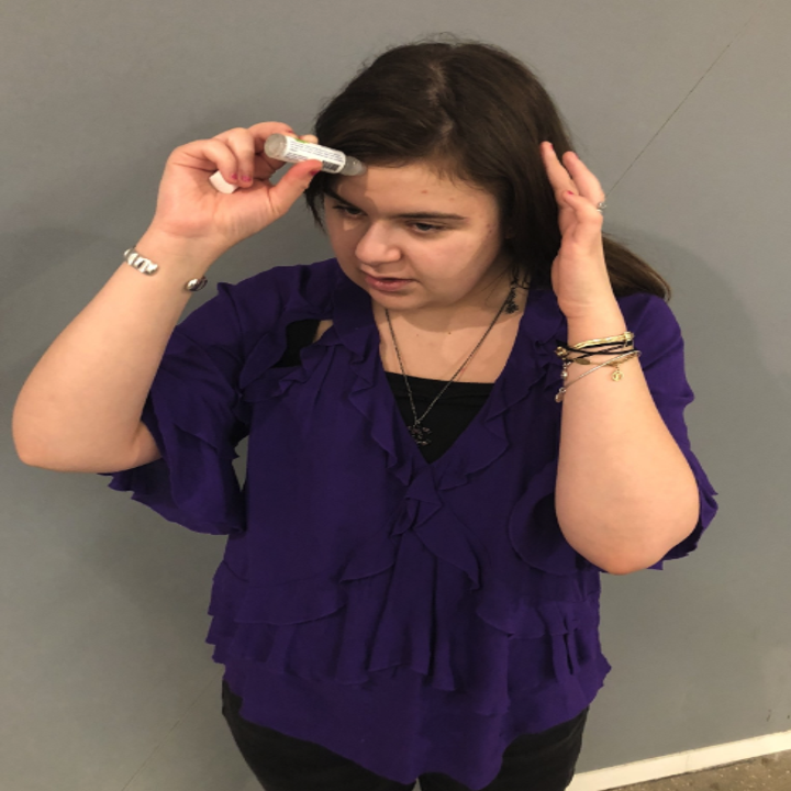 a buzzfeed editor applying the oil to their forehead