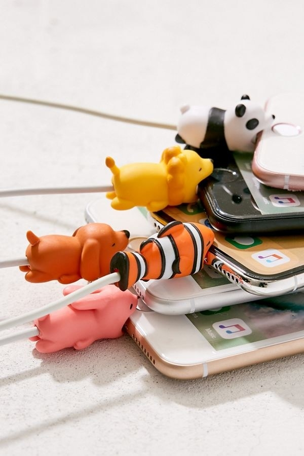 A panda, lion, clownfish, dog, and rabbit animals over a cable their mouth's open on phones