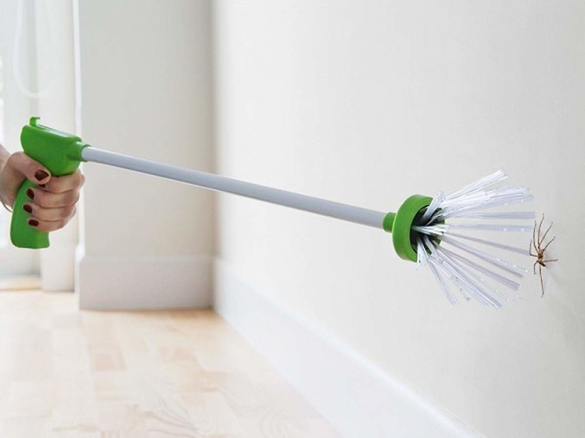 a model holds a handle with long pole and bristles at the end of it and uses it to catch spider on wall