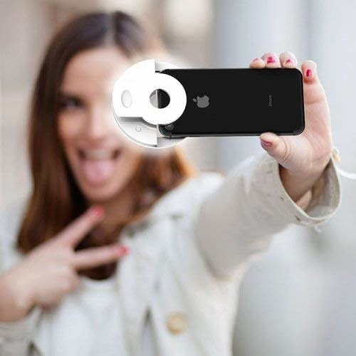 model takes selfie with clip on light