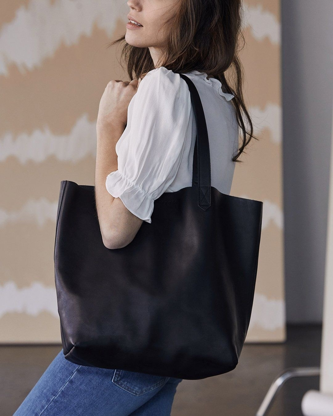 Model with the leather tote bag in black over their shoulder