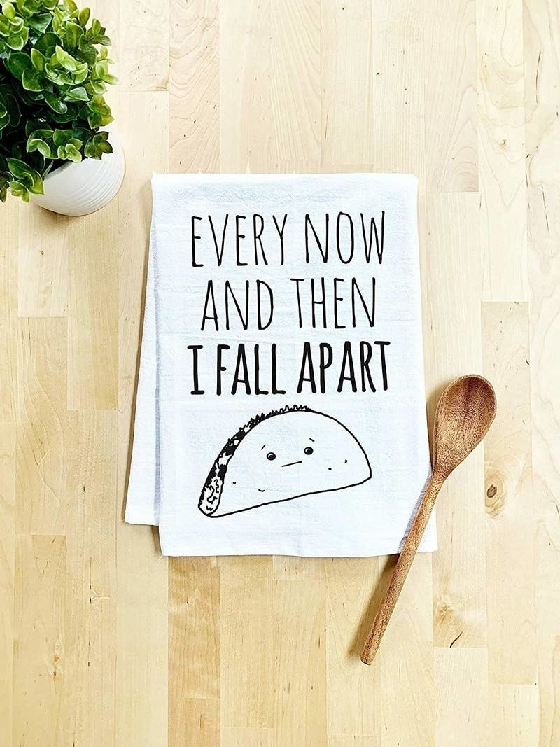 "white dish towel with an illustration of a taco on it and the words ""Every Now And Then I Fall Apart"""