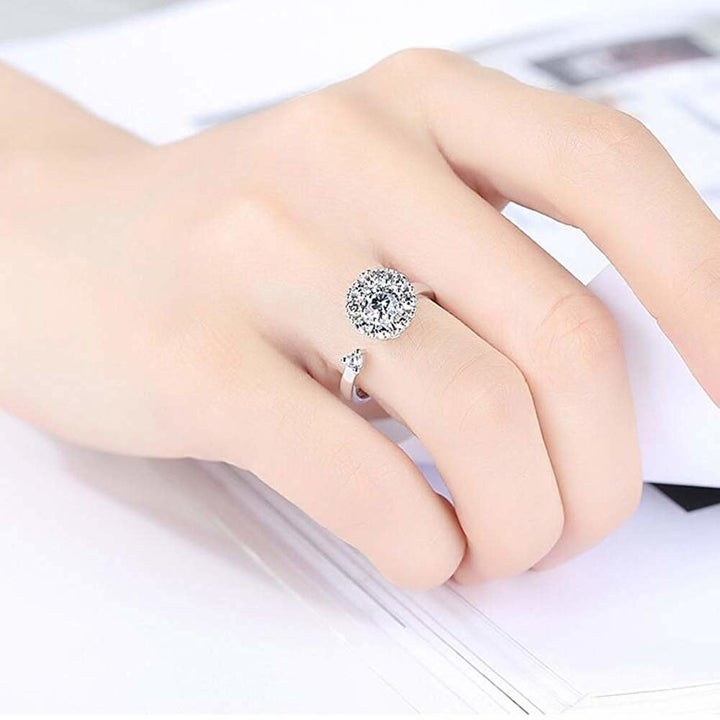 model wears open ring with large stone