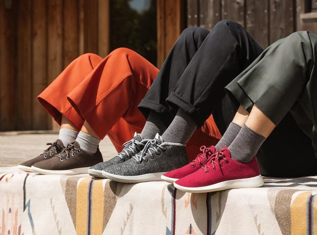 Models wearing the sneakers in brown, gray, and red