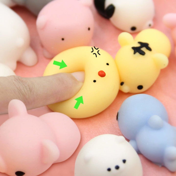 a finger squishing a yellow toy shaped like a chick