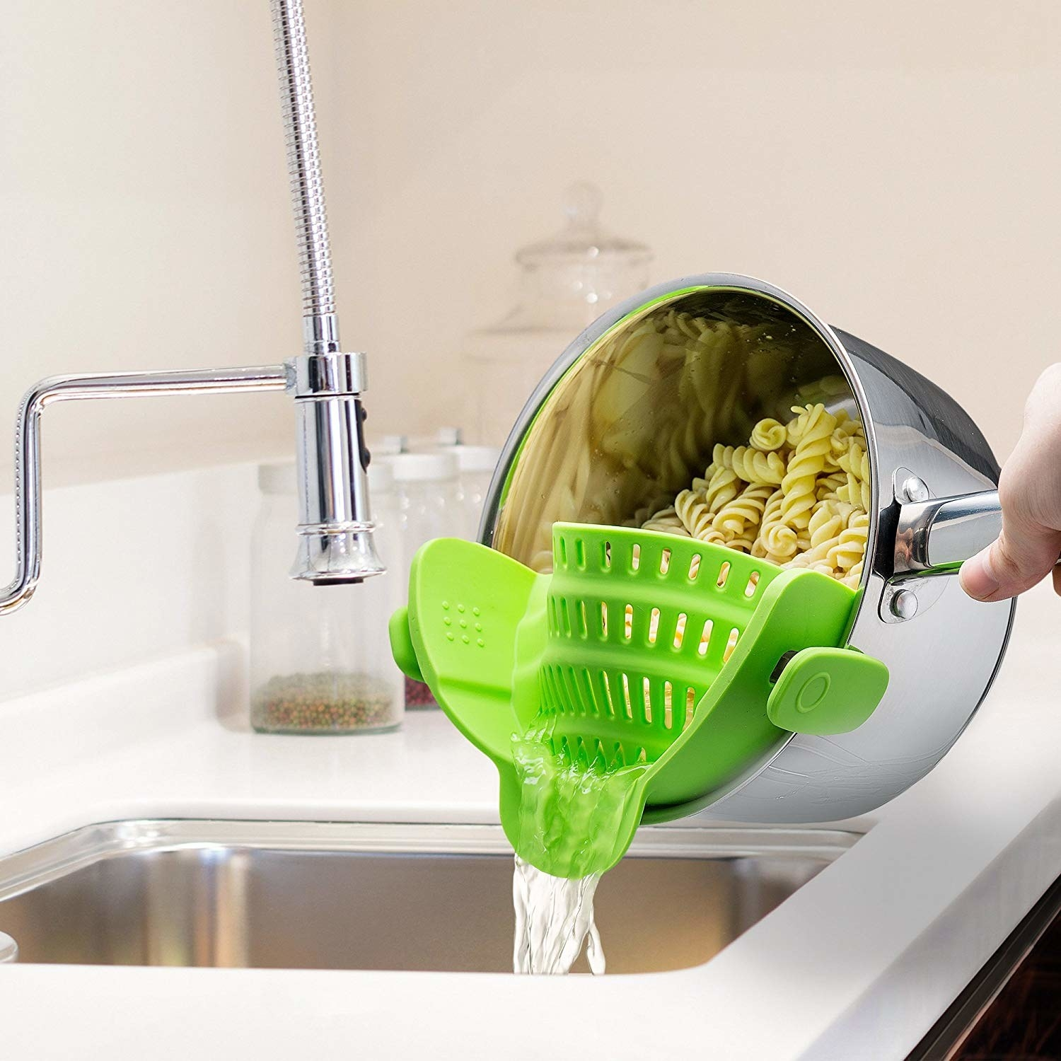 A model pouring out pasta water with one hand, with the green strainer clipped on the pot