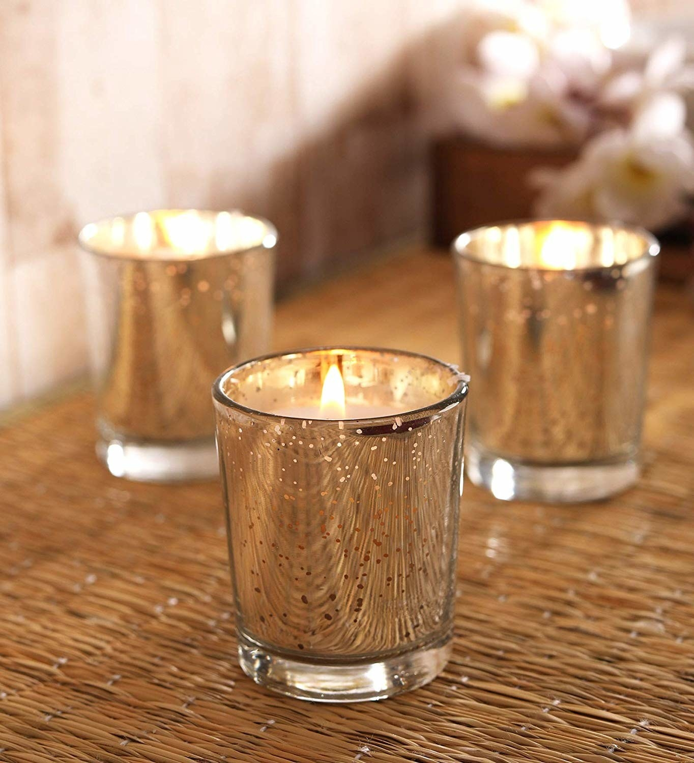 A set of three metallic glass holders on a table with lit candles inside them