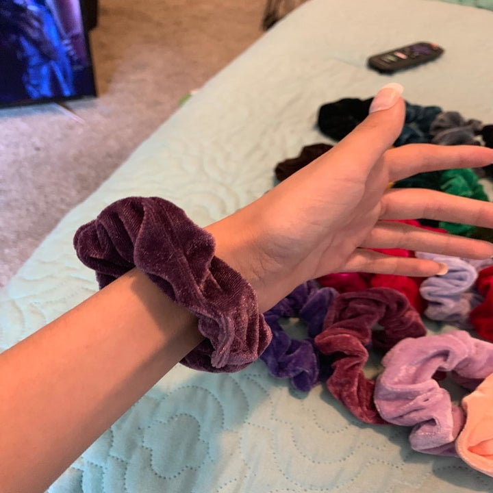 Reviewer wearing purple velvet scrunchie on their wrist