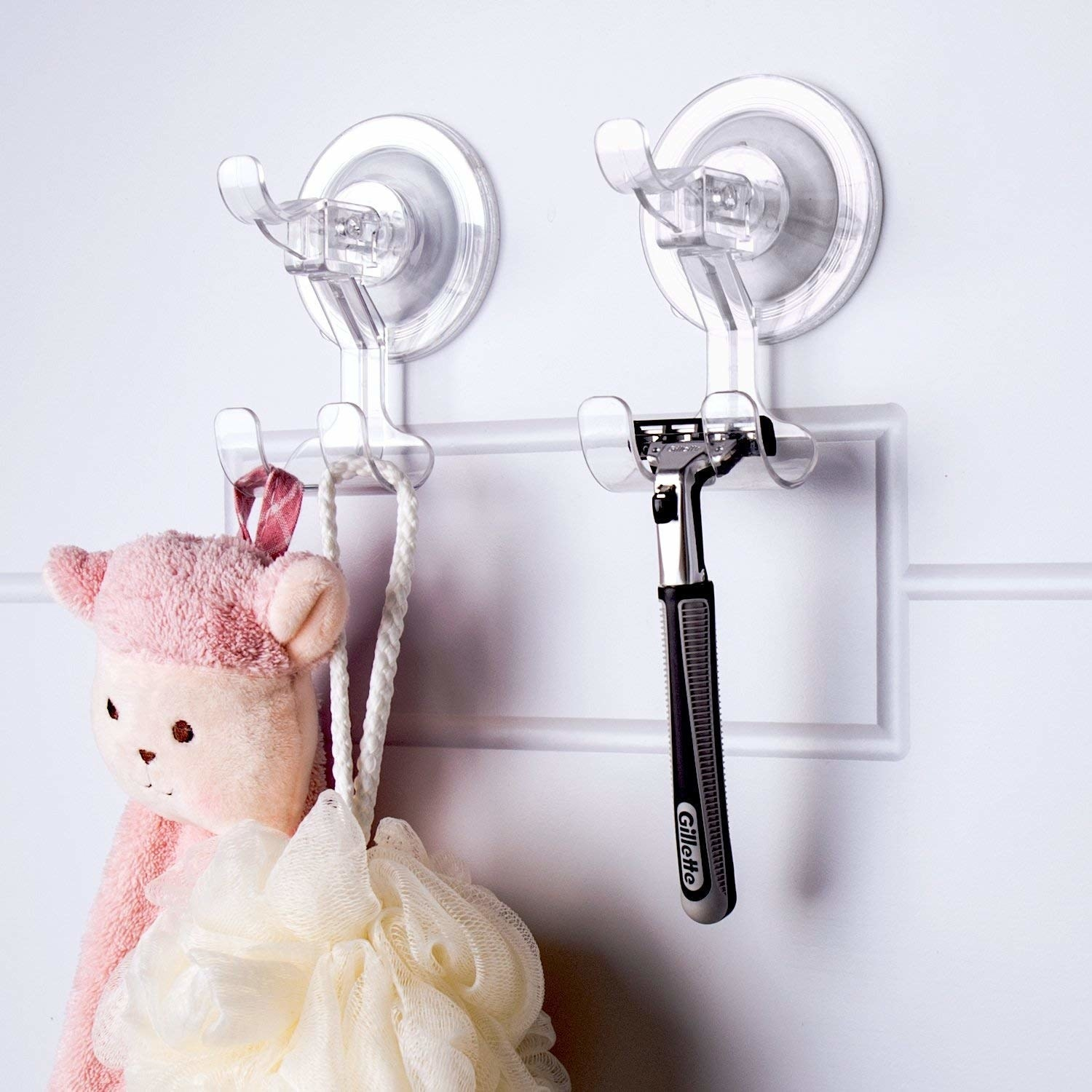 Round suction cup hooks stuck to a wall and holding up a razor and loofah