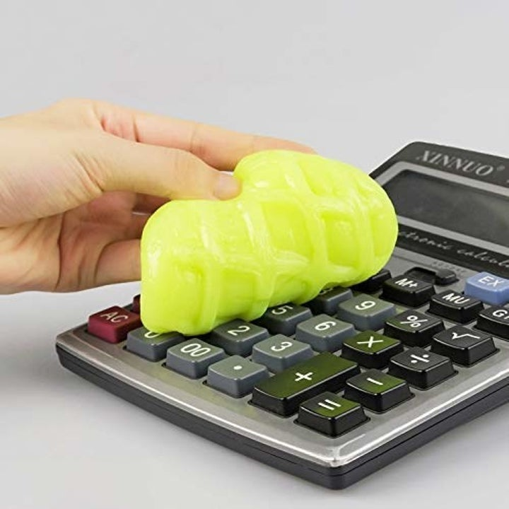 A model using a ball of the yellow gel to clean in between calculator keys