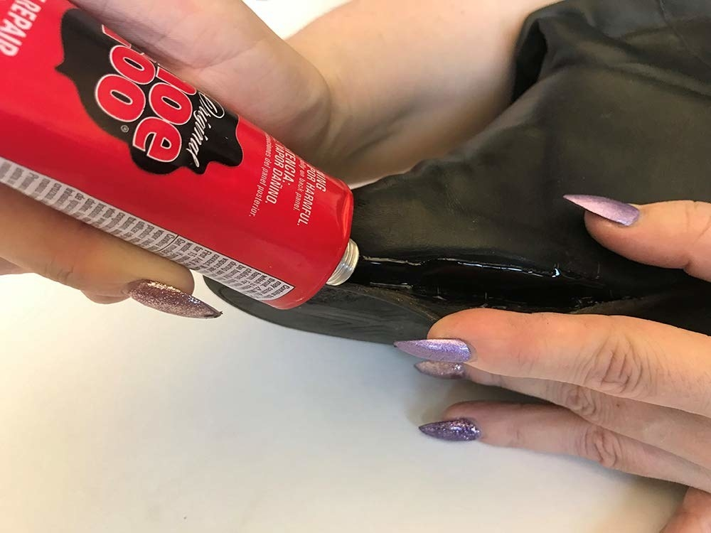 A reviewer squeezing a tube of black shoe goo onto the side of boots