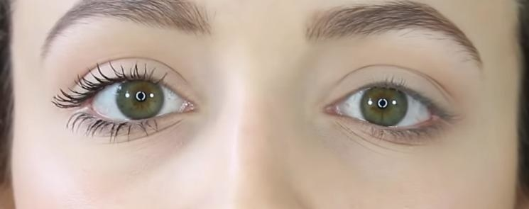 A reviewer showing barely-there lashes on one eye and longer slightly curled lashes on the other eye