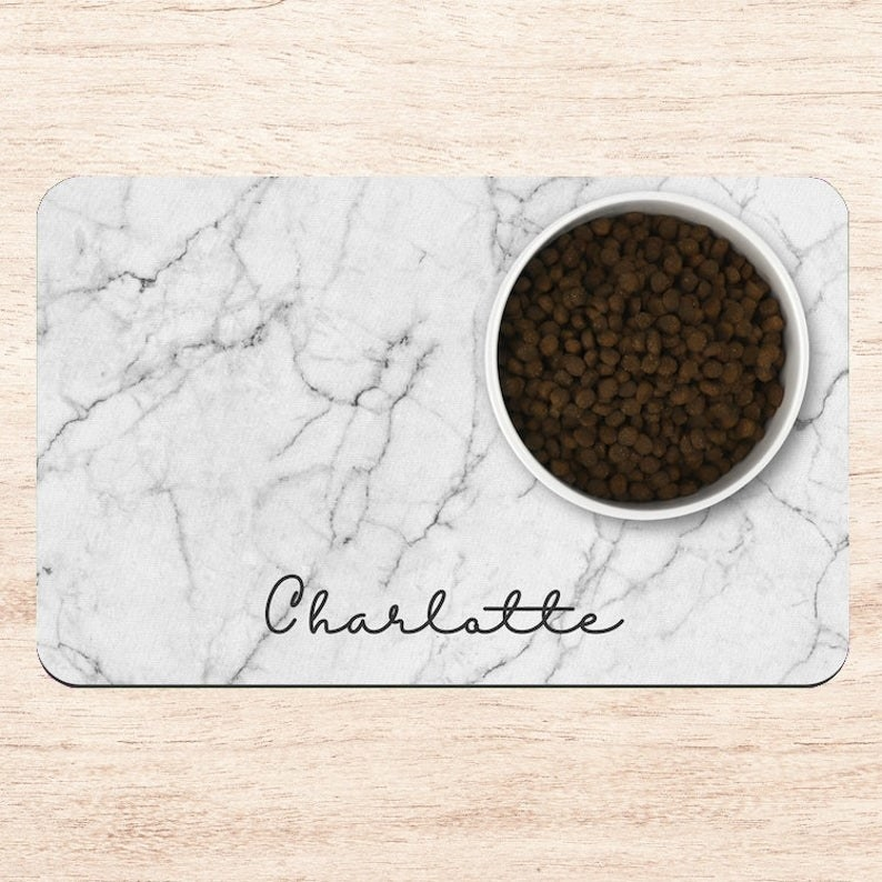 a rectangular marble print mat with the name charlotte written on it in script