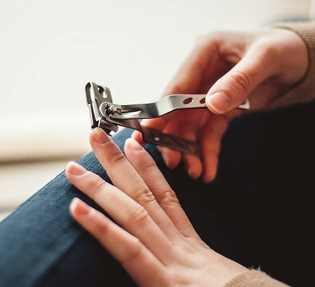 person using swivel nail clippers to clip nails