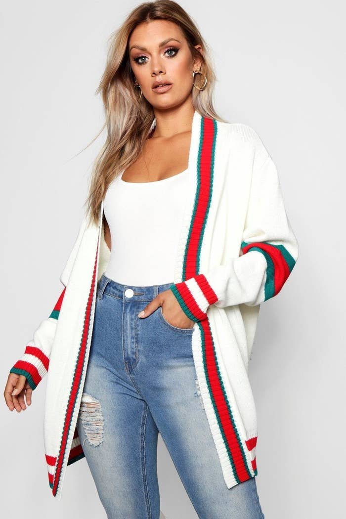 a model in a white open cardigan with red and green stripes as accents