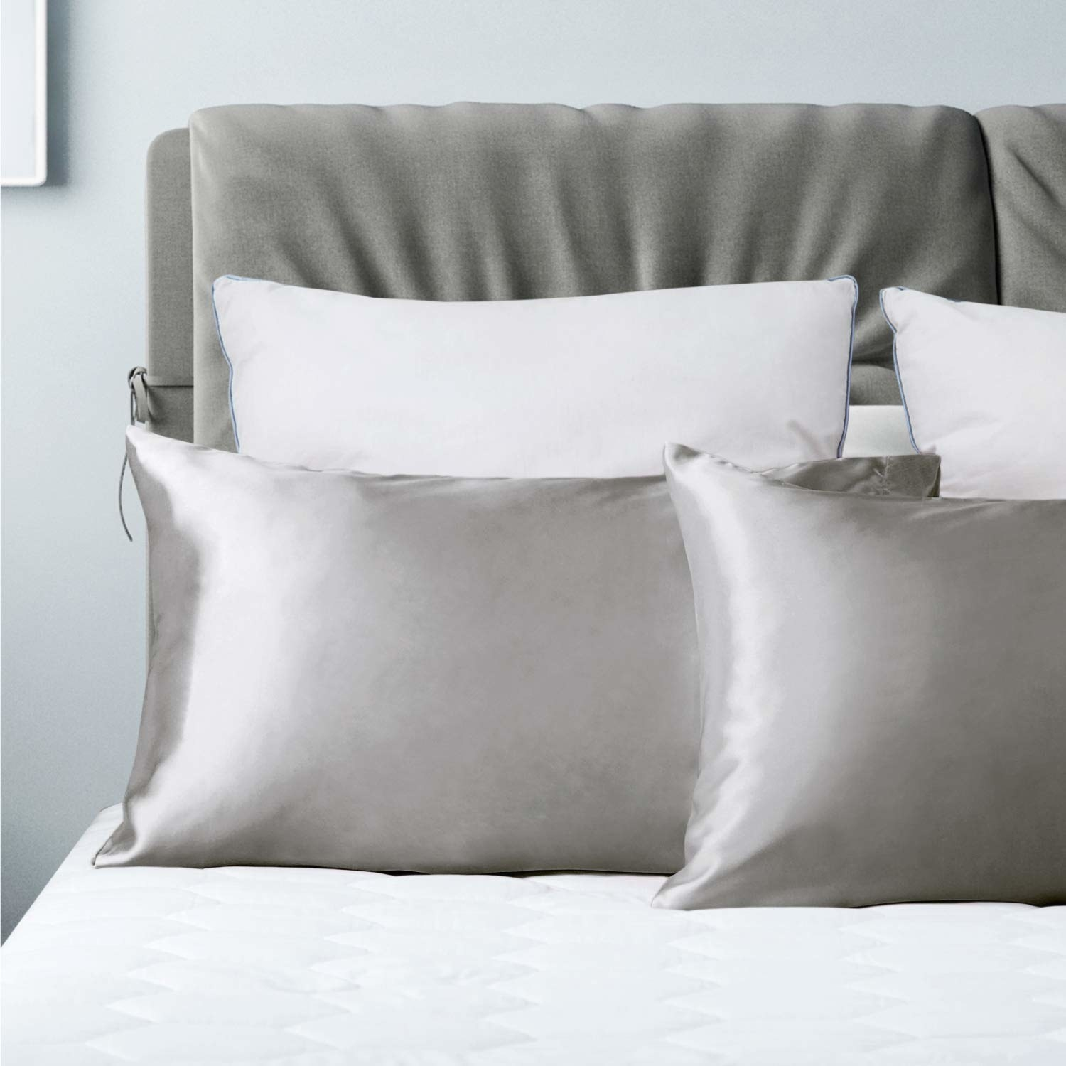 bed with gray satin pillowcases on two bed pillows