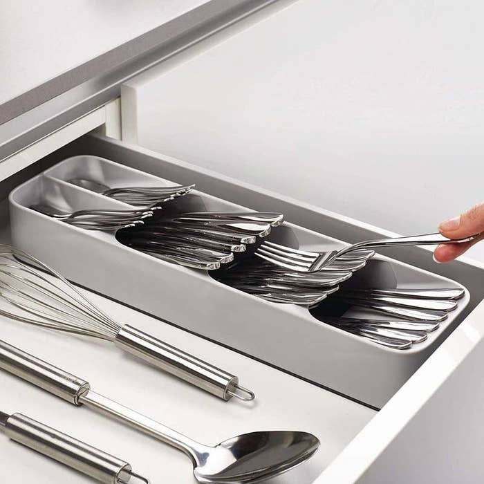 Long rectangular tray in grey with four different sections with silverware in each
