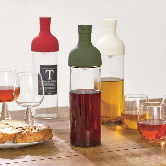 Three bottles with clear bottoms and different-colored silicone tops in olive green, white, and red with tea in two of the bottles