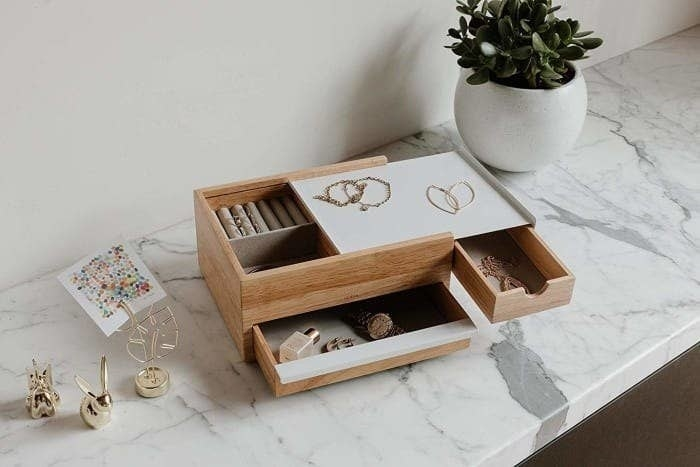 A wood jewelry box with a long skinny drawer in the front a smaller drawer on the side and a white lid that pulls back to reveal jewelry storage