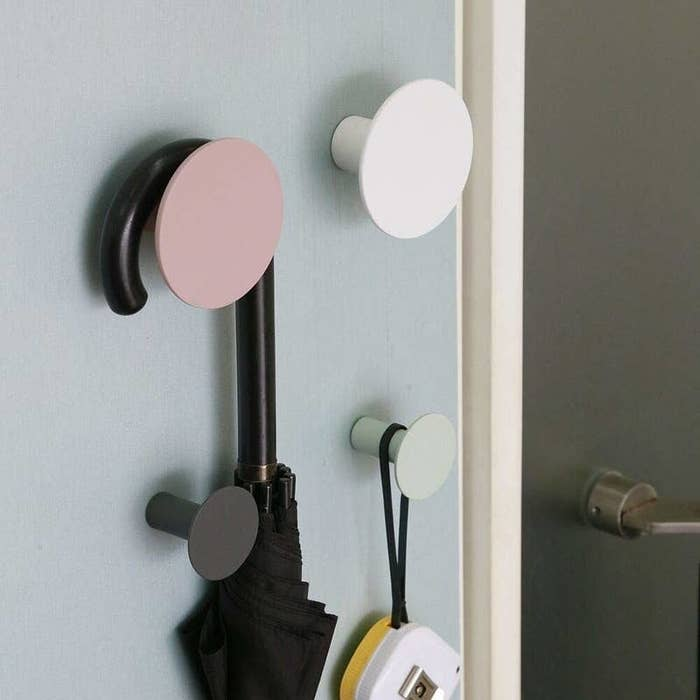 Two large circle hooks in pink and white and two small circle hooks in black and mint below with assorted things hanging from them
