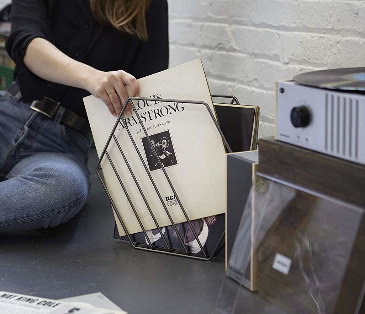 A person putting a record into the hexagonal record holder
