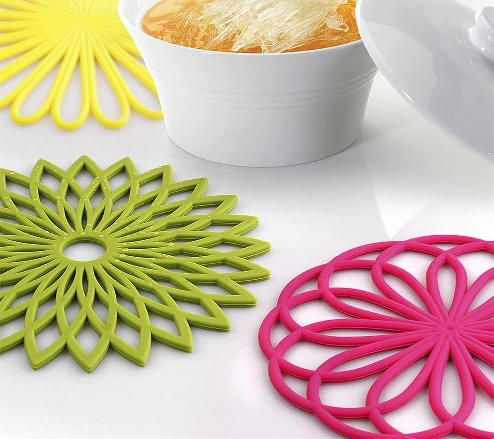 Bright pink, green and yellow flower trivets sitting on a table