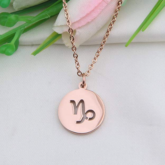 A pendant necklace with the Capricorn sign on it