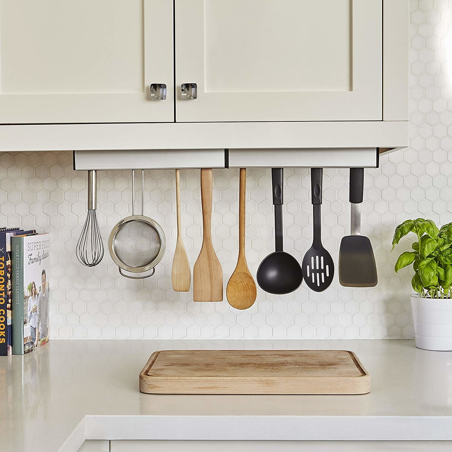 The floating kitchen organizer attached to the bottom of a cabinet with assorted kitchen utensils hanging from it