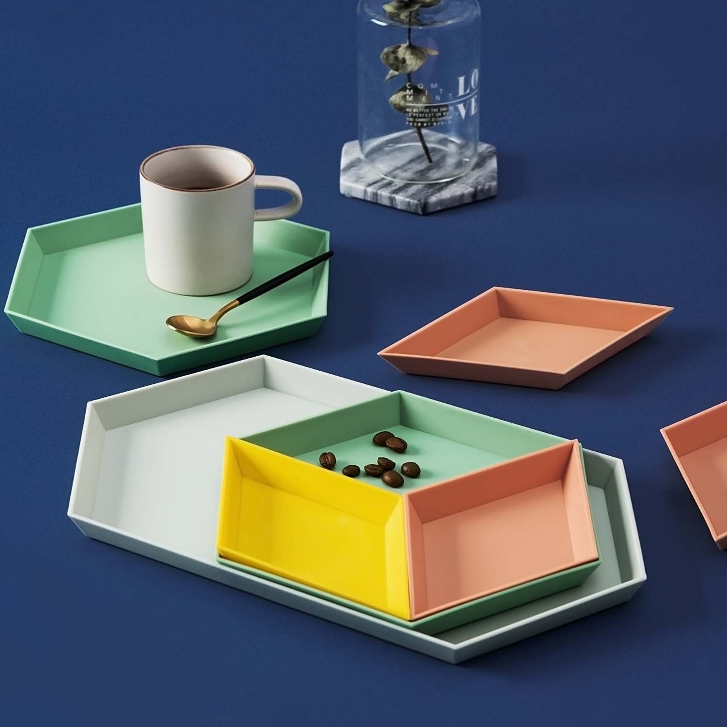 The four trays in different sizes withing each other in yellow, orange, green, and white