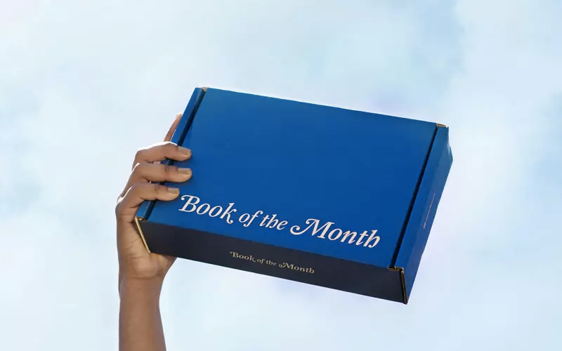 hand holds cardboard box that says book of the month