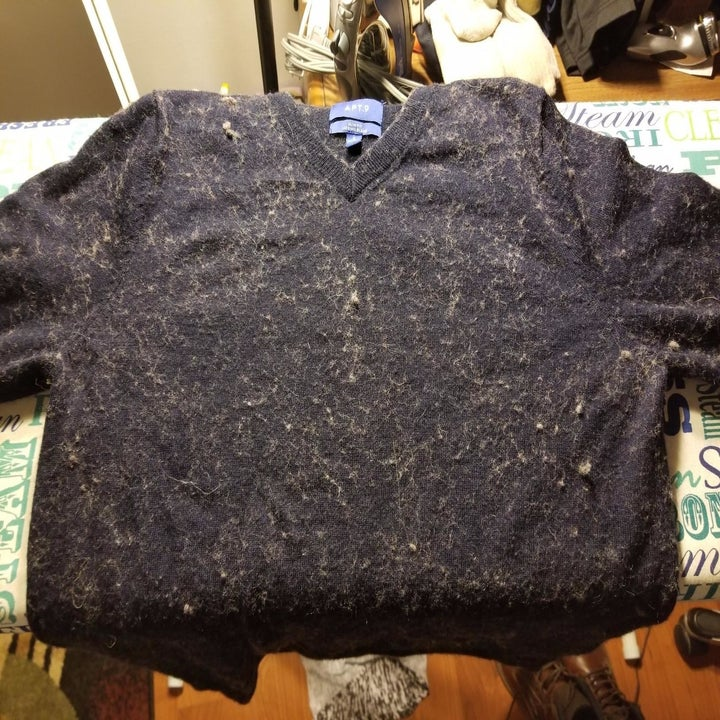Before photo of reviewer's dark gray sweater, which is covered in white lint and pilling
