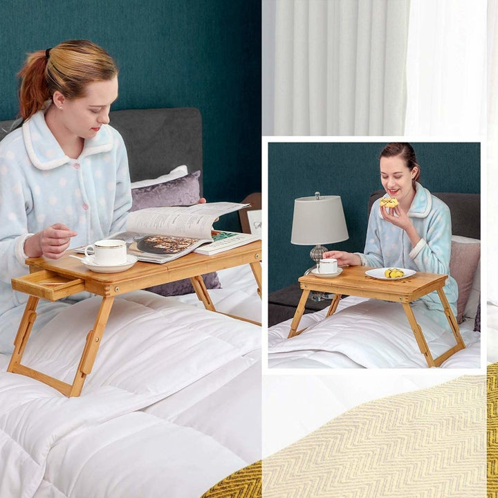 model sitting on bed with laptop desk and fitting a magazine and snacks on it