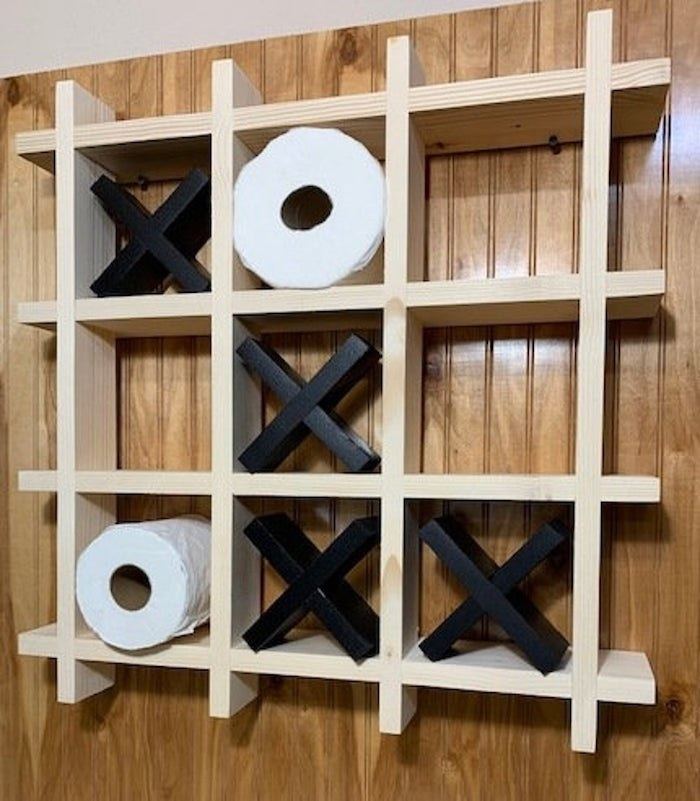 a wooden tic tac toe board attached to a wall with wooden X's in it and toilet paper rolls that serve as the o's