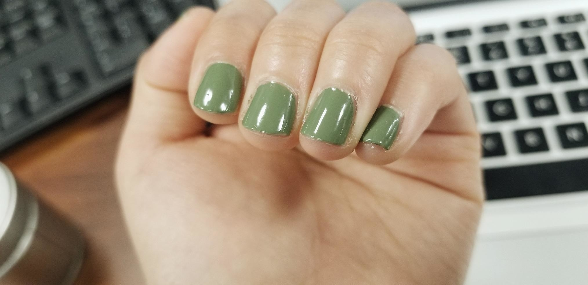 A reviewer showing their olive green nails looking shiny