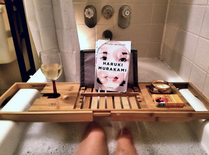 the bamboo tray over a bathtub filled with soapy water holding a book, tablet, wine glass, and candle