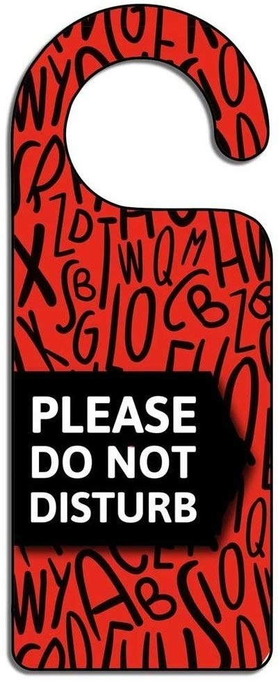 "A red and black door hanger with the words ""Please Do Not Disturb"" on it"