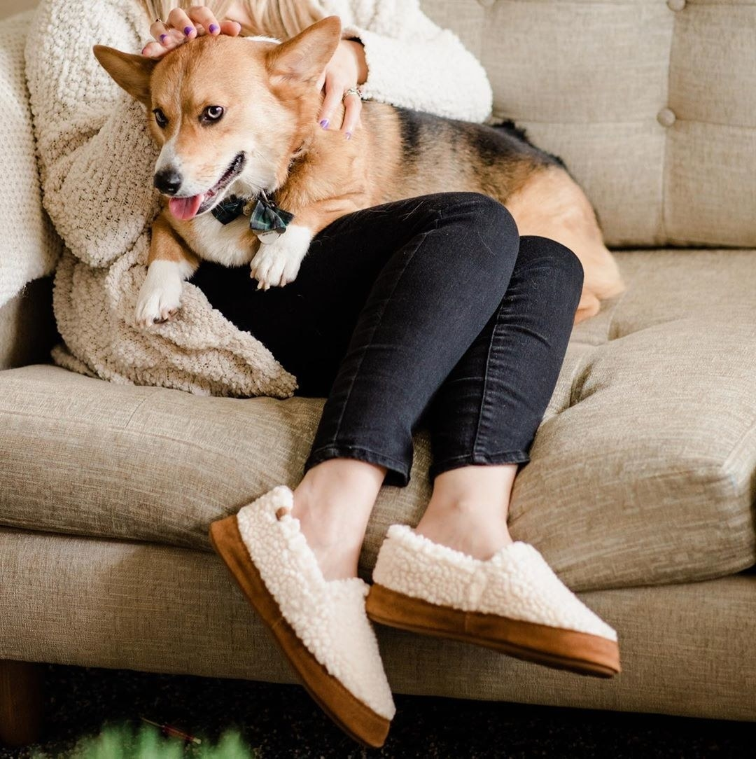 Model wearing the slippers with brown bottoms and white fuzzy shearling fabric on the top and sides