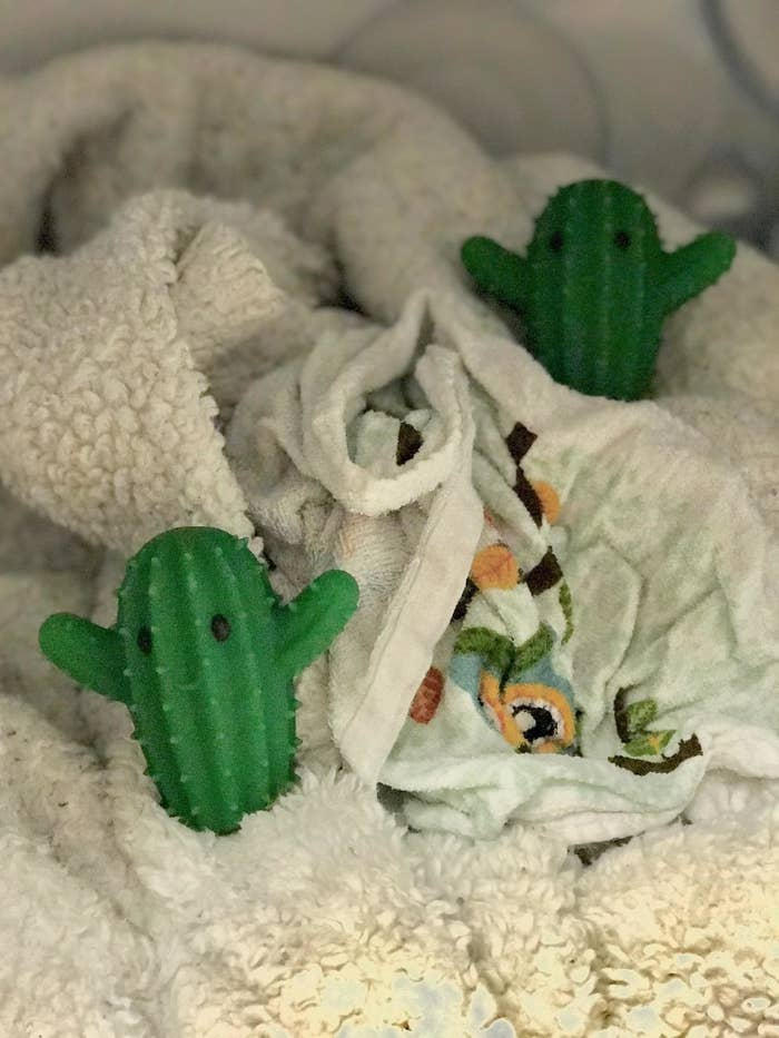 The green dryer balls in a reviewer's pile of towels