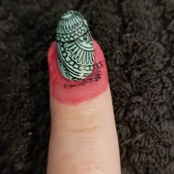 Reviewer photo of cuticle tape with some stray nail art stamp marks on it