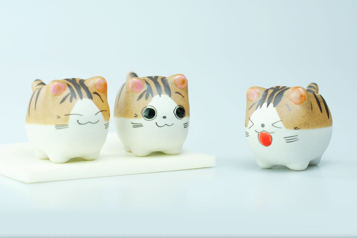 Three tiny striped cat planters with different faces