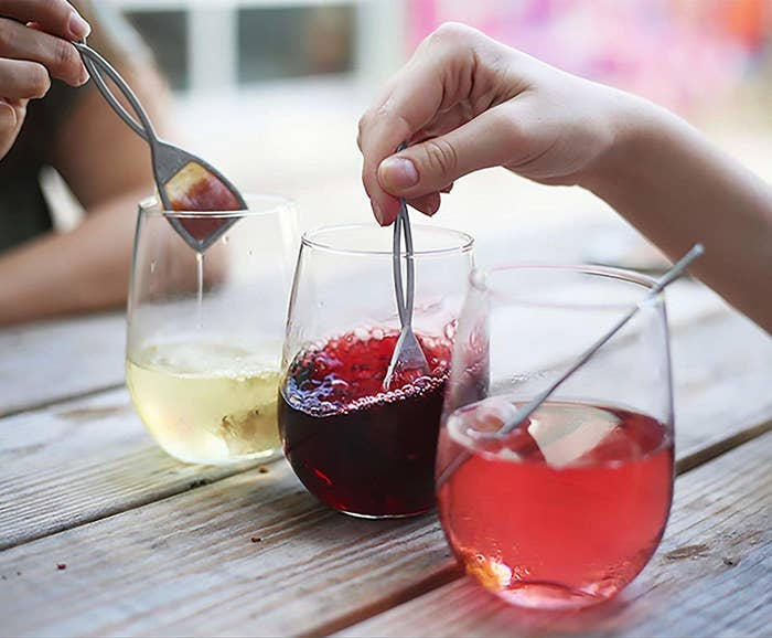 hands dip tea bag like devices into wine